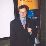 Person im Anzug, steht und spricht in ein Mikrophon.
