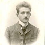 Porträt von Mathias Koener. Hochstehende Haare, leichter Schnurrbar, karierte Jacke mit Knöpfen, Stehkragen.