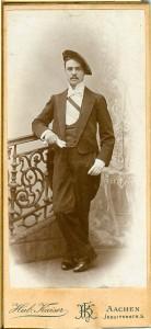 Junger Mann, mit Mütze und Schärpe und Handschuhen vor Geländer