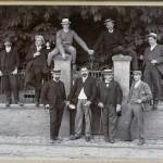 9 Männer. Vier vor einer Mauer mit Tor und Geländer, drei auf der Mauer stehend, zwei auf den Torpfosten sitzend.