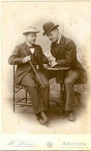 Zwei Studenten mit Hüten, sitzend an einem Tisch mit Bierkrug