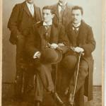Vier Männer, zwei vorne sitzend mit Melone, zwei hinten stehend