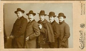 5 Männer mit Mantel und Hut hintereinander