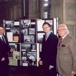 Drei Männer, Herr Mueller von der Stadt Aachen, der Redner und der Luxembuger Konsul Braun stehen im Rathaus vor einer Kollage mit Fotos aus unserer Geschichte
