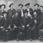 Zehn Personen in in zwei Reihen, vier sitzend in der ersten, 6 dahinter stehend. Links eine Treppe, rechts ein Stuhl, vorne in der Mitte ein Dackel