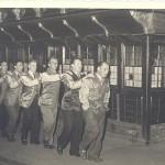 8 Personen bilden eine Polonaise vor dem Postwagen 1954