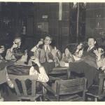 8 Studenten sitzen 1954 rund um einen Tisch, die Füsse auf demselben und prosten einander zu