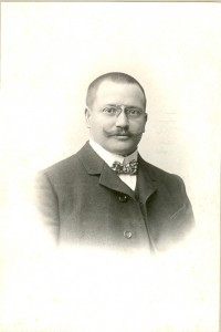 Porträt eines Mannes mit Kurzhaarschnitt, wilhelminischem Schnurrbart, Nickelbrille, Stehkragen, Fliege
