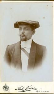 Portrait eines bärtigen Studenten mit Vereinsmütze und rot-weiss-blauer Schärpe
