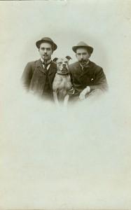 Zwei Männer mit Peiffe und einem Hund