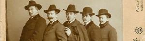 5 Männer im Mantel, hintereinander stehend mit Hut.