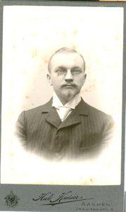 Mann mit Spitzbart und Nickelbrille im gestreiftem Anzug mit Stehkragen