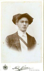 Glattrasierter junger Mann, mit Anzug, rot-weiss-blauer Schärpe, Barrett und Brille.